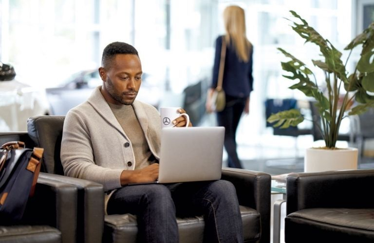 Man at car dealership on laptop