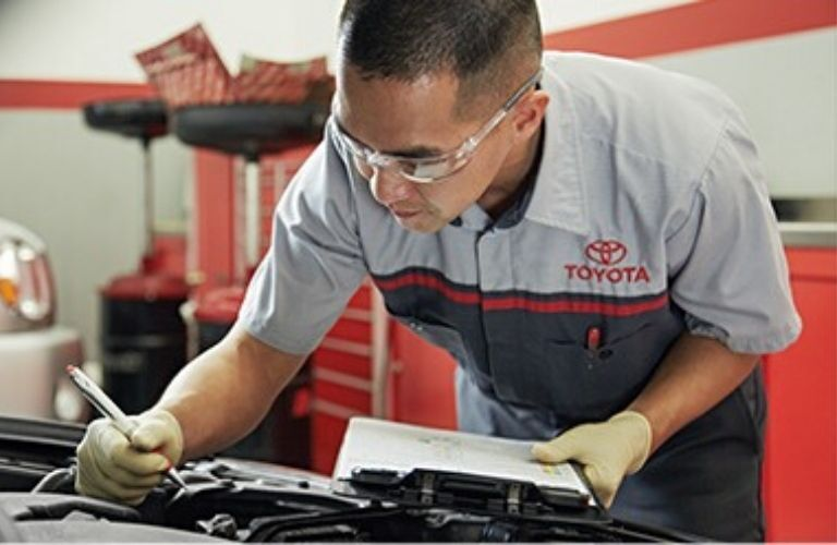 A Toyota Service Technician filling out a multi-point vehicle inspection