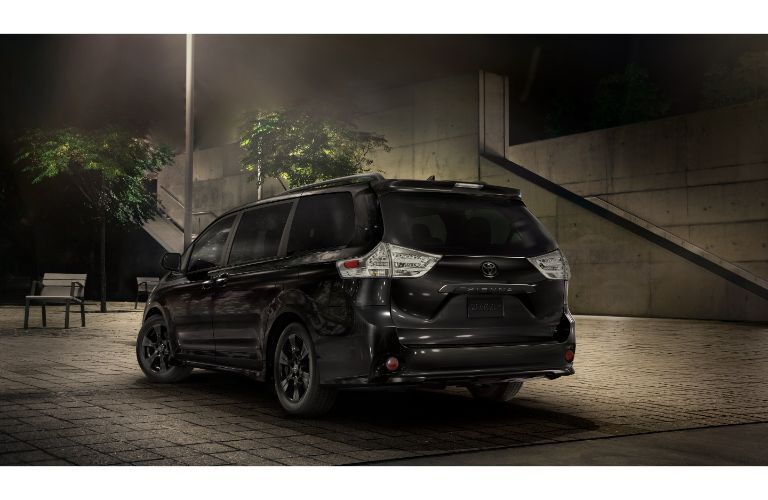 2020 Toyota Sienna exterior rear shot with midnight black metallic paint color parked under a streetlight near a subway station entrance