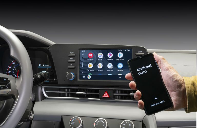 A photo of a person using the wireless smartphone connectivity in the 2021 Hyundai Elantra.