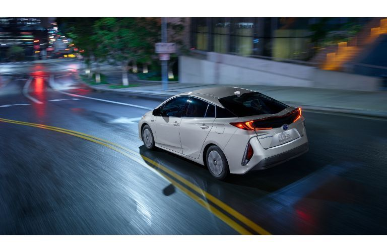 2020 Toyota Prius Prime exterior overhead shot with gray paint color driving through a city on rain-slicked roads at night