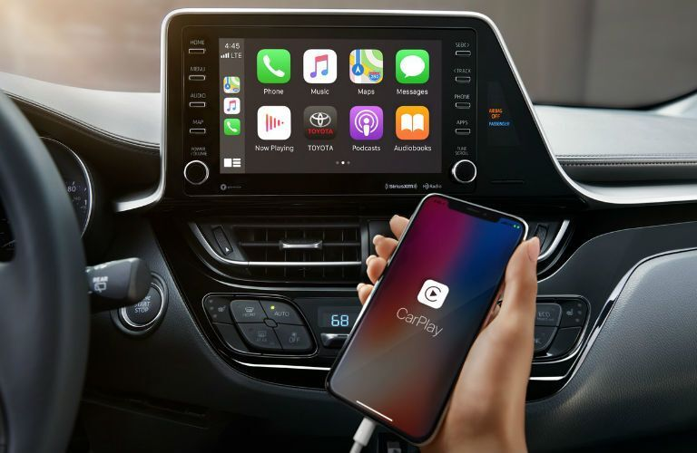 A photo of a person connecting their phone to the infotainment system.