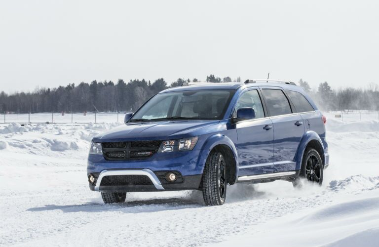 Blue 2020 Dodge Journey driving on snowy terrain