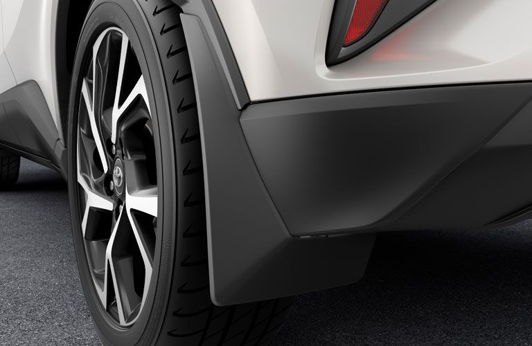 An image of the rear tire and bumper of a white 2020 Toyota C-HR.