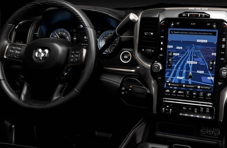 Interior view of the steering wheel and touchscreen display available inside a 2020 RAM 2500
