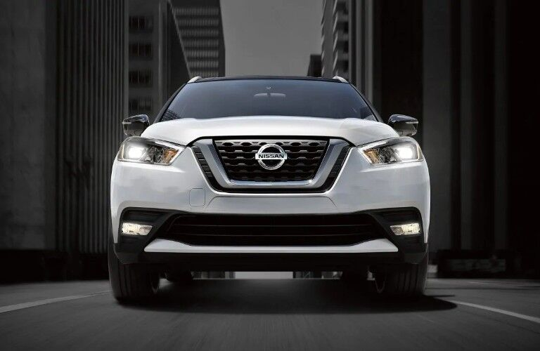 Front angle of a white 2019 Nissan Kicks on a dark background