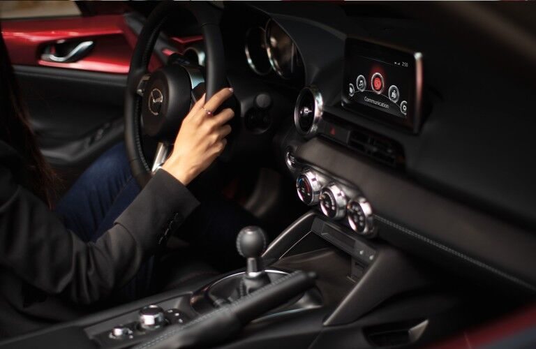 The steering wheel and center console of a 2020 Mazda MX-5 Miata.