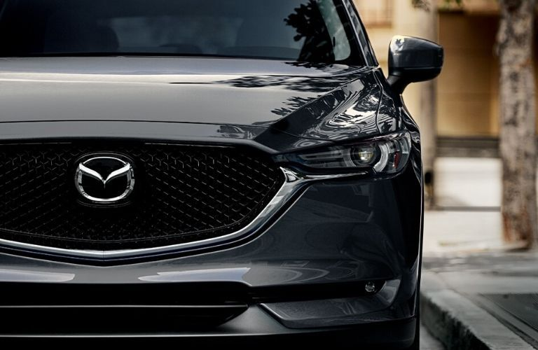 Closeup view of the front grille and headlights on a gray 2020 Mazda CX-5