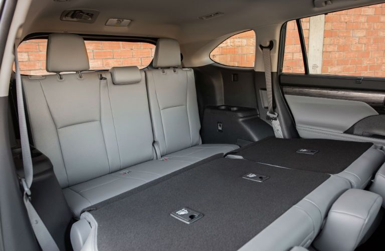 An interior photo of the middle row of seats folded down in the 2020 Toyota Highlander.