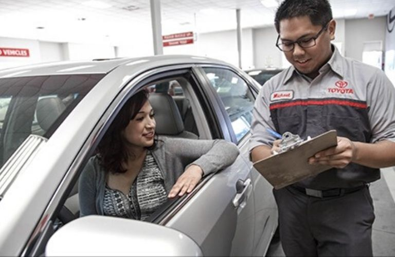 Image of a Toyota service technician covering the details of the multi-point inspection with a customer