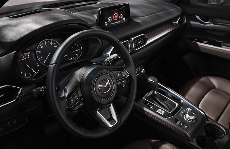 Interior view of the steering wheel and touch screen display inside a 2020 Mazda CX-5