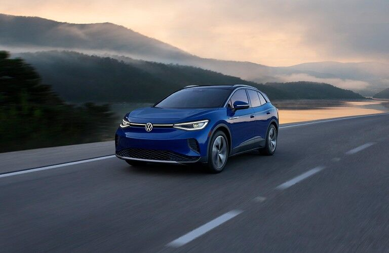 The front view of a blue 2021 Volkswagen ID.4 driving away from mountains.