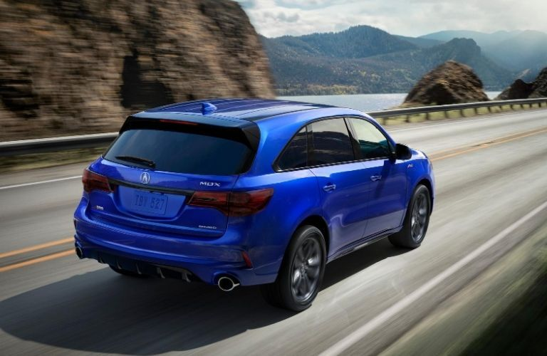 2020 Acura MDX rear quarter view as it drives on a highway