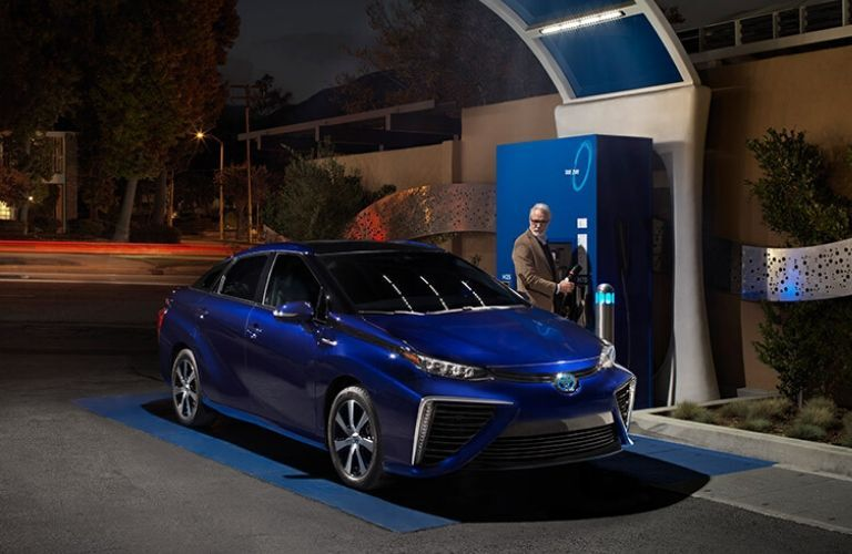 man charging 2020 Toyota Mirai at night