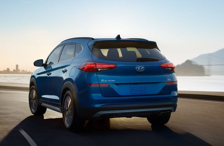 Rear driver angle of a blue 2020 Hyundai Tucson driving by a lake with a city in the background