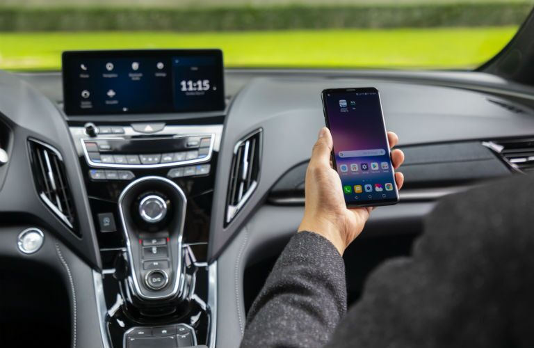 A photo of a person connecting their smartphone to the infotainment system equipped in the 2020 Acura RDX.