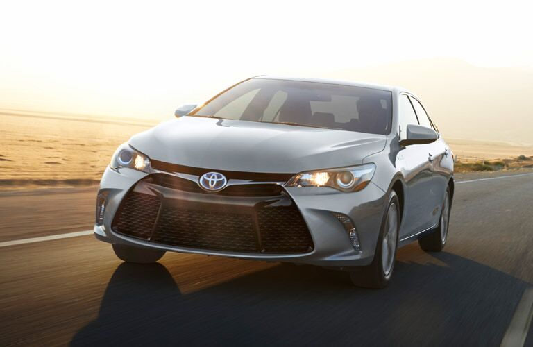 A gray 2016 Toyota Camry driving down a road.