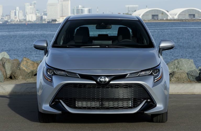 A head-on photo of the 2020 Toyota Corolla Hatchback parked by some water.