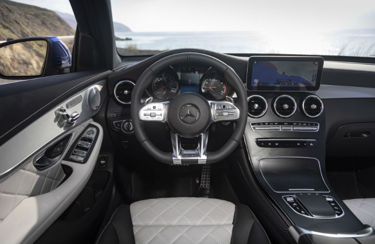 2020 MB GLC Coupe interior front cabin steering wheel dashboard and touchscreen display in front of lake
