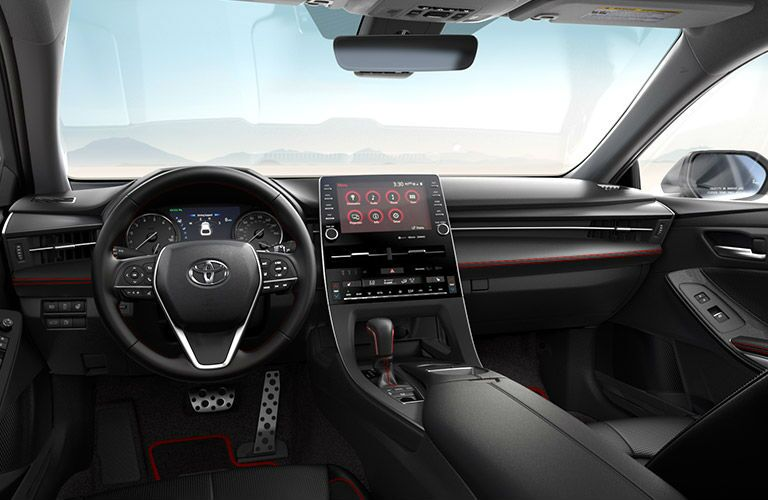 The front interior view of the steering wheel and center console inside a 2020 Toyota Avalon.