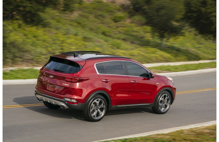 2021 Kia Sportage exterior rear shot with dark red paint color driving on a highway near green hills