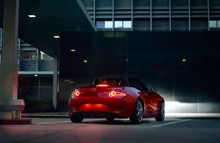 The rear vview of a red 2020 Mazda MX-5 Miata parked in a city at night.