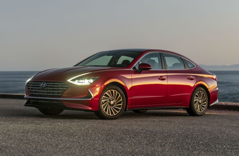 The front and side view of a red 2020 Hyundai Sonata parked on a beach.