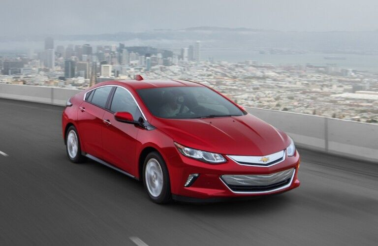 Front passenger angle of a red 2019 Chevrolet Volt driving on a bridge with a city in the background