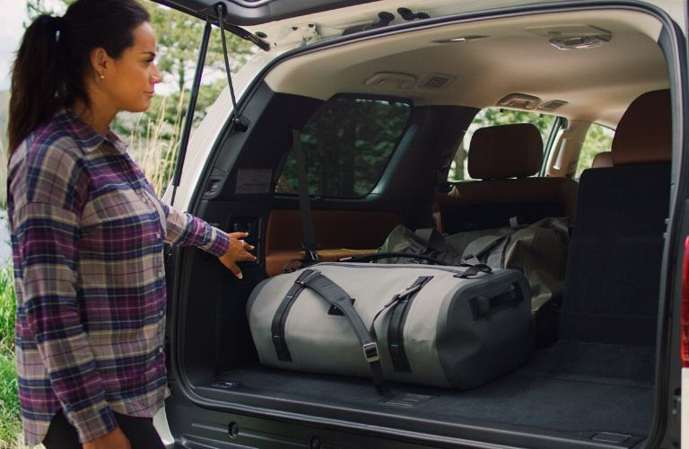 woman loading cargo into rear of 2020 Toyota Sequoia