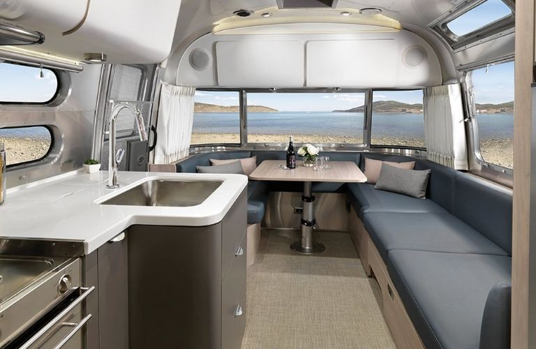 interior of 2020 Airstream Globetrotter showing couch, kitchen, and eating area