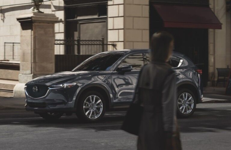 A person walking in front of a gray 2021 Mazda CX-5 parked across the street.