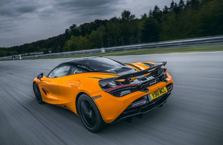 2020 McLaren 720S orange exterior driver side rear driving on track stormy sky