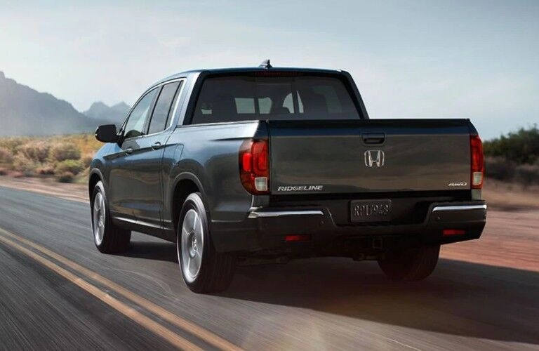 Rear driver angle of a grey 2019 Honda Ridgeline driving down a rural road