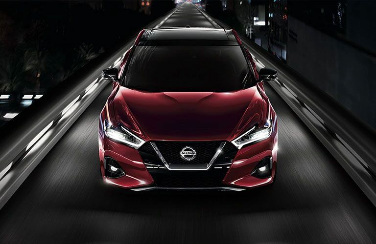 A red-colored 2021 Nissan Maxima driving on a lighted bridge
