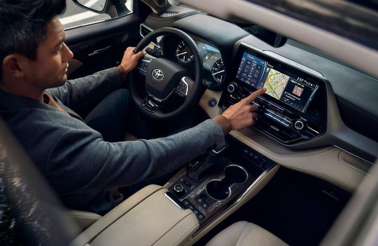 Interior view of a many using the navigation system while driving inside a 2020 Toyota Highlander