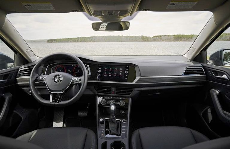 Front row interior of the 2020 Volkswagen Jetta with the steering wheel and touchscreen display in view