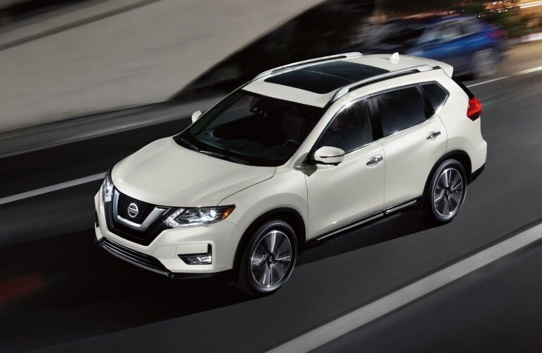 Front driver angle of a white 2020 Nissan Rogue driving on a street