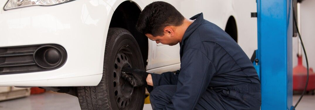 Mechanic working on a tire on a white car