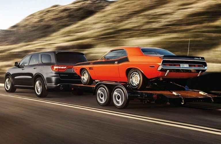 Exterior view of a black 2020 Dodge Durango towing a trailer with a classic muscle car on it