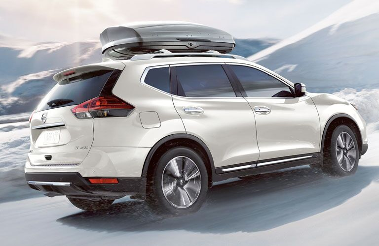 White 2020 Nissan Rogue driving with luggage on top of vehicle on a snow-covered road with snow in the background