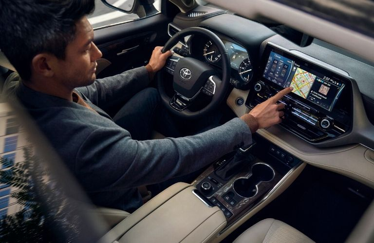 Interior view of a man adjusting the navigation system while driving inside a 2020 Toyota Highlander