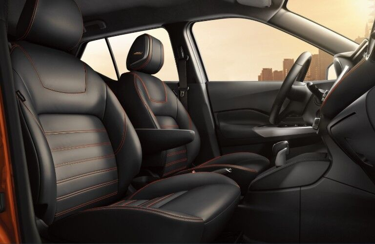 Front passenger angle of the black front row interior with orange stitching in the 2019 Nissan Kicks