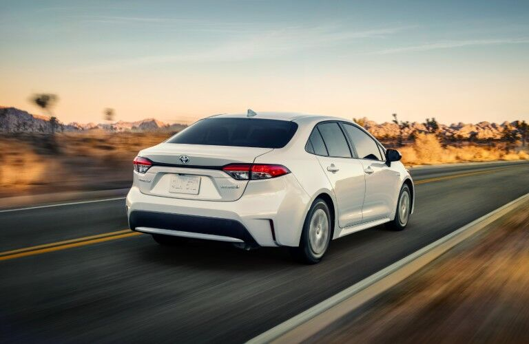 Rear passenger angle of a white 2020 Toyota Corolla driving with a sunset in the background