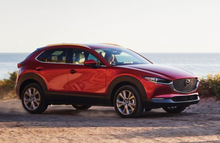 The front and side view of a red 2021 Mazda CX-30 parked on the beach.