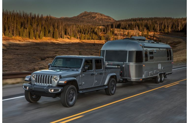 2020 Jeep Gladiator exterior shot with gray metallic paint color towing a trailer on a country road near a forest