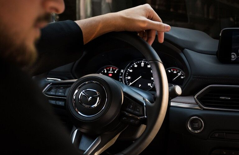 Hand gripping steering wheel of 2019 Mazda CX-5
