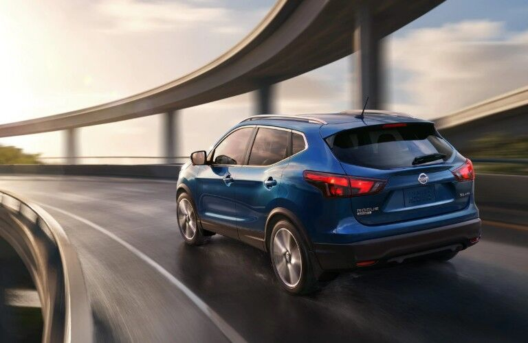 Rear driver angle of a blue 2019 Nissan Rogue Sport driving on a bridge