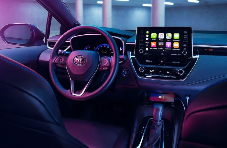 Interior view of the steering wheel and touchscreen display inside a 2020 Toyota Corolla