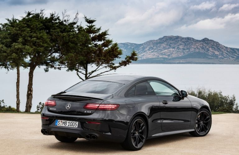 2021 MB E-Class Coupe exterior rear fascia passenger side in front of water and mountain