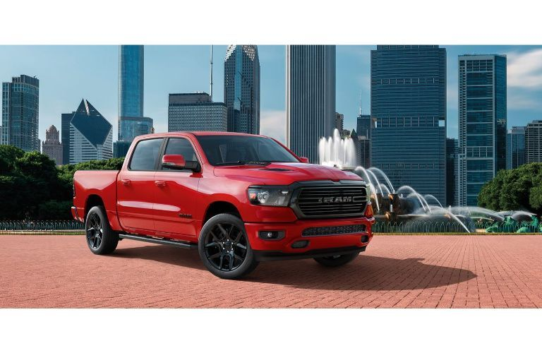 2020 Ram 1500 Laramie exterior shot with red paint color parked in a city park cobblestone path near a fountain with a cityscape skyscraper background